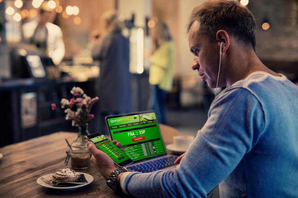 Ein Mann verfolgt verschiedene Sportwetten auf einem Laptop und Smartphone in einem Café
